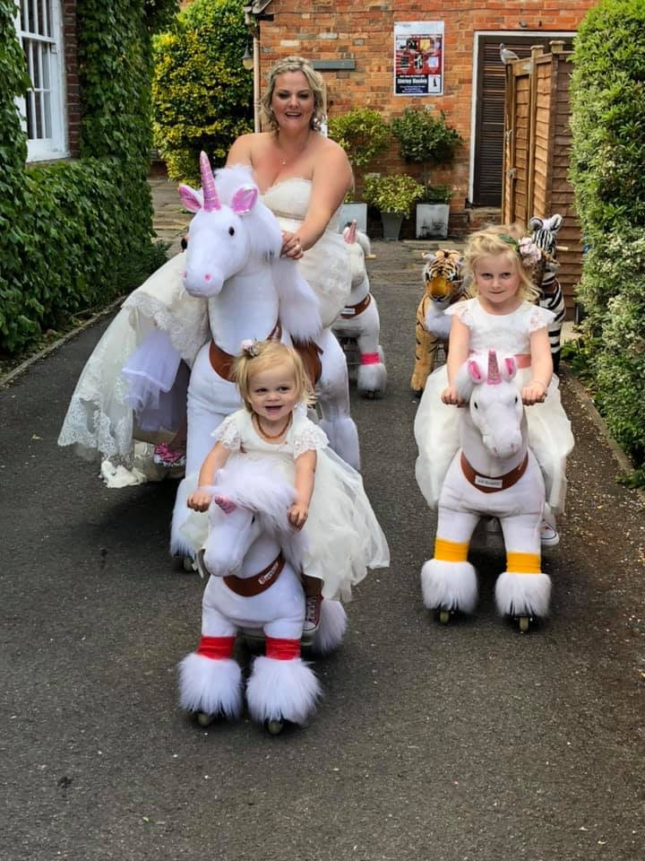 Picture showing Bride and Bridesmaid riding mechanical ponies